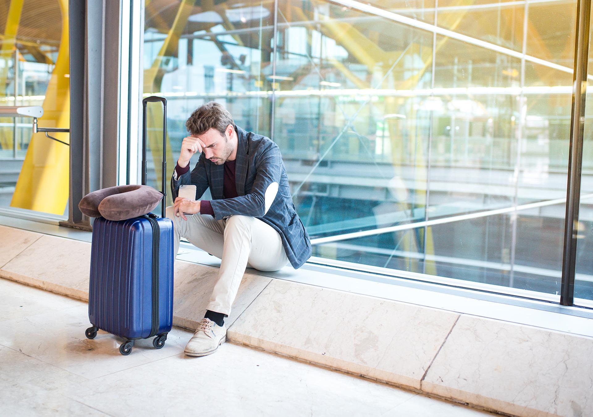 Mann sitzt unglücklich am Flughafen, da sein Flug ausfällt