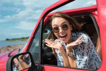 Frau glücklich im Auto während eines Roadtrips