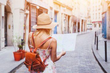 Touristin läuft mit Karte durch eine Straße