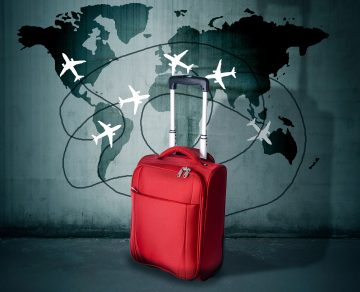 Koffer vor Weltkarte mit Flugzeugen