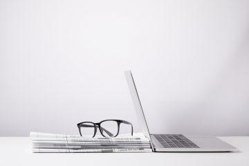 Bild mit Laptop und gestappelten Zeitungen, auf denen eine Brille liegt