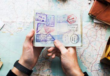 Jemand hält einen Reisepass über einer Weltkarte