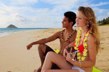 Pärchen sitzt am Strand auf Hawai