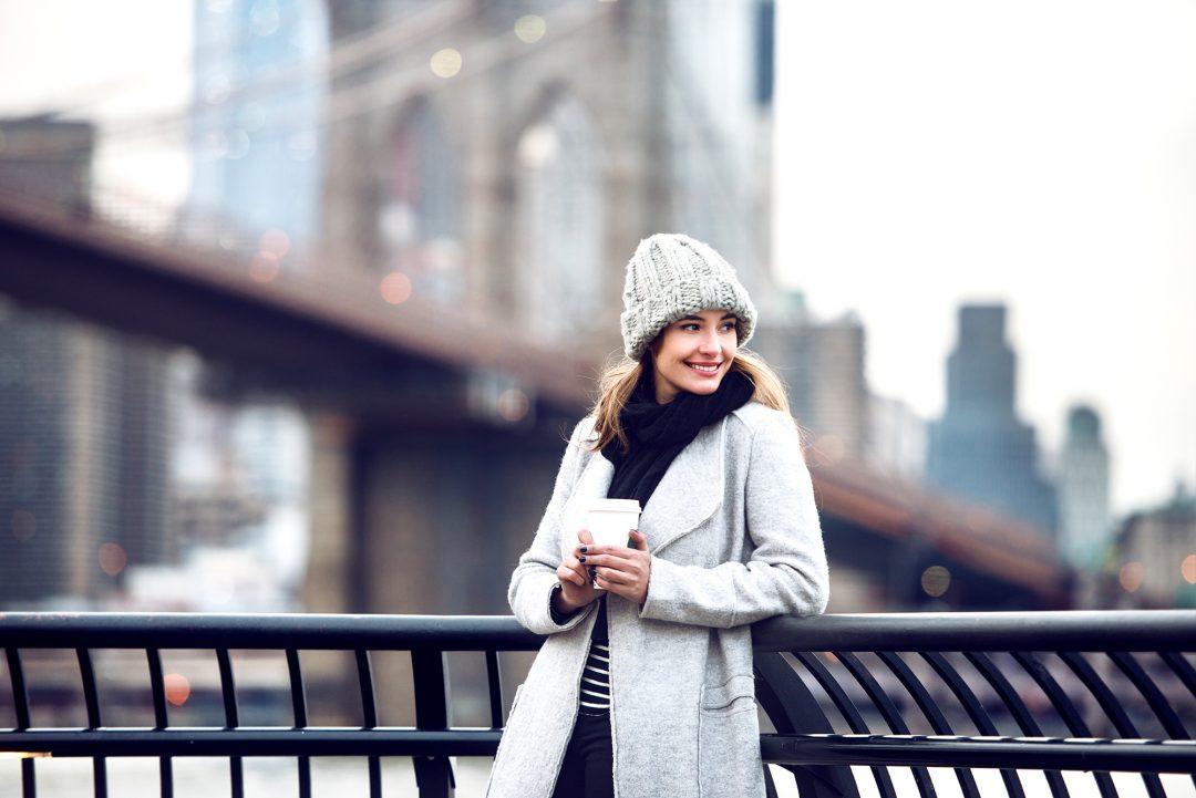 Dame genießt Shopping und Aussicht in New York an der Brooklyn Bridge